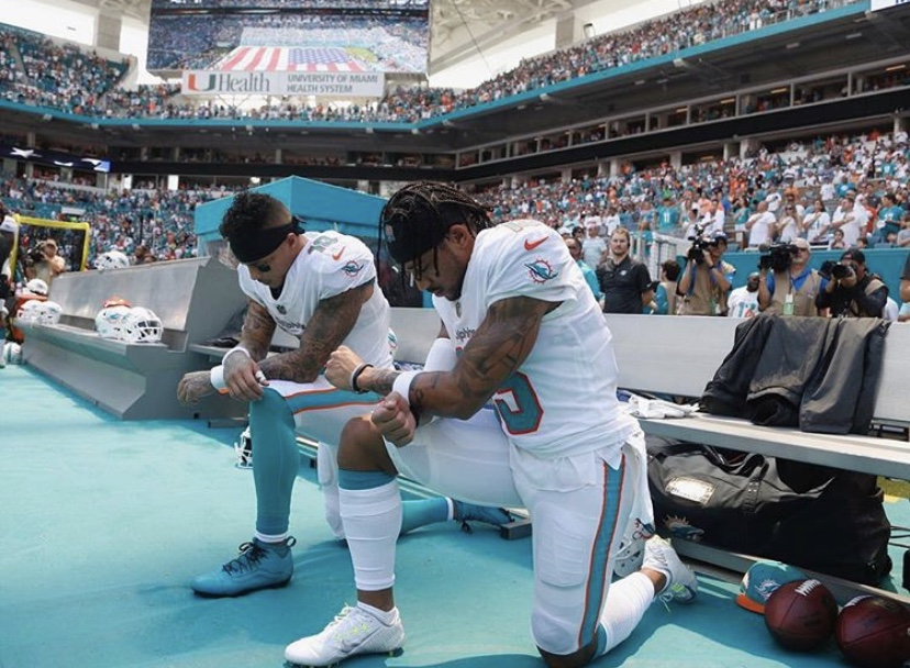 Two members of the Miami Dolphins kneeling during an NFL game